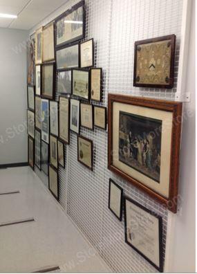 framed artwork hangs on wall mounted art racks